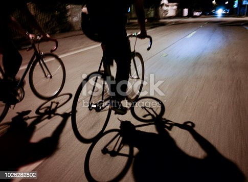 Shadows of 2 people riding bicycles in motion with contrasting light and dark shadows at night.