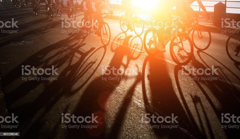 Shadows of bike riders at dawn stock photo