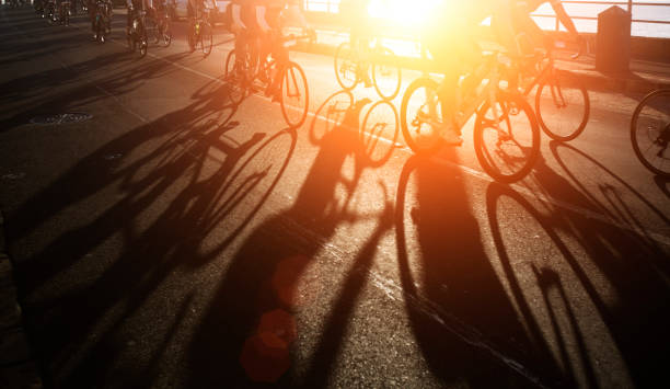 shadows of bike riders at dawn - cycling stock pictures, royalty-free photos & images