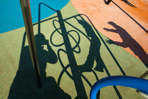 Shadows of children and adults on playground,
