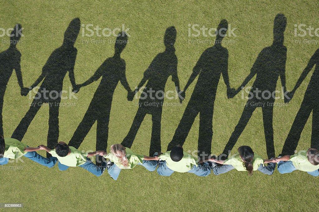 Ombre di bambini tenendo le mani in una riga foto stock royalty-free