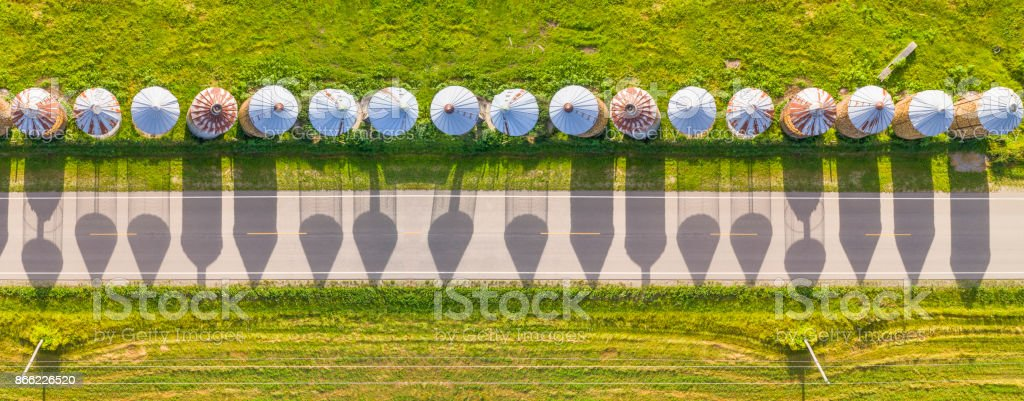 Shadows of corn cribs decorate scenic country road. stock photo