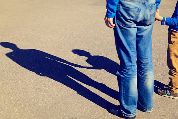Shadows of father and son holding hands stock photo