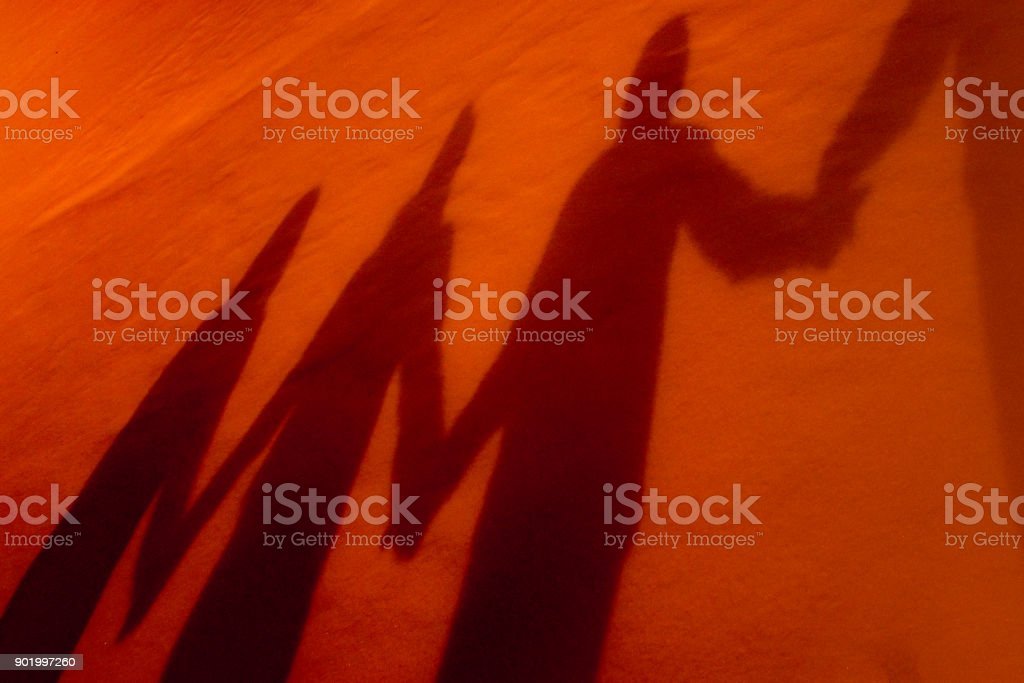 Shadows of four people holding hands Shadows of four people cast by winter sunlight upon snow.  All  are dressed in warm winter clothing.  They are holding hands.   Original image's temperature and tint have been manipulated.  Grainy image.  Grand Island, NY. A Helping Hand Stock Photo