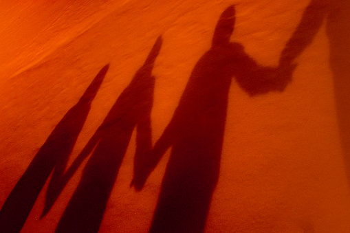 Shadows Of Four People Holding Hands Stock Photo - Download Image Now