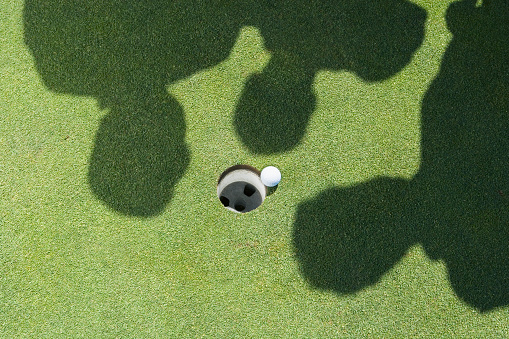 istock Shadows of golfers over golf ball next to hole 1035128032