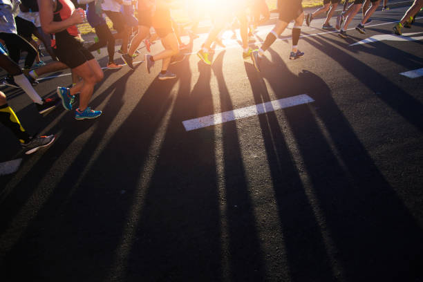 shadows of joggers legs on the road - marathon stock photos and pictures