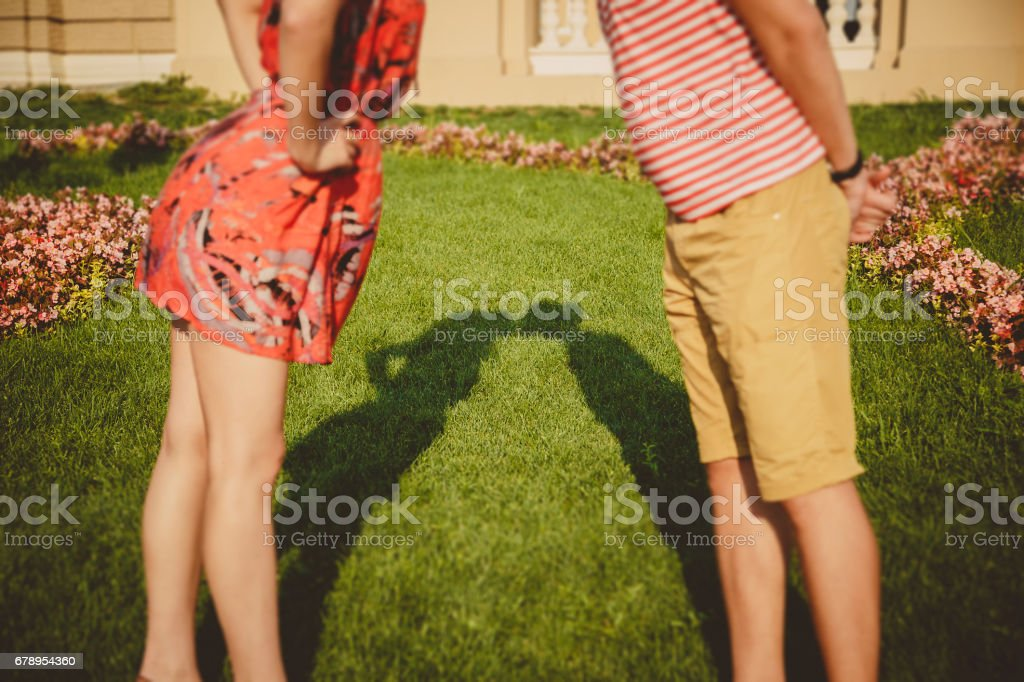 Shadows of kissing couple forming their silhouette on the grass. Happy young couple kissing in the flower park outside stock photo