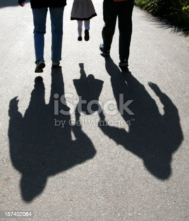 shadows behind two adults carrying a child on a sidewalk