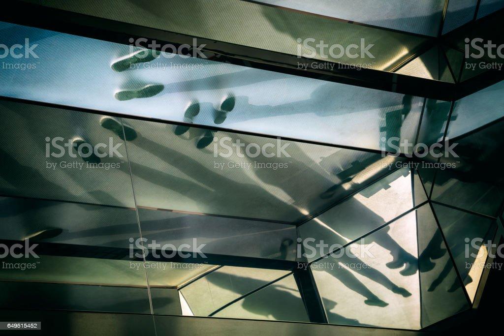 Schatten der Menschen und Füße durch das Glas Bodenbelag sichtbar – Foto