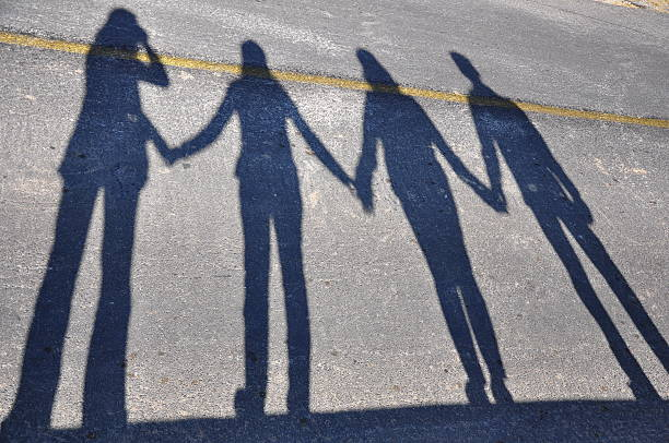 Shadows of people holding hands Shadows of people holding hands arcane stock pictures, royalty-free photos & images
