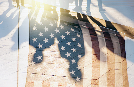 istock Shadows of People in a street and Flag of The USA as Background concept toned Picture 979963456