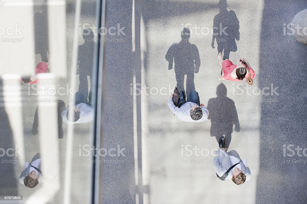 Shadows of people walking from directly above stock photo