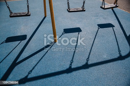 The shadows of thee empty swings falling onto a blue safety surface in a park