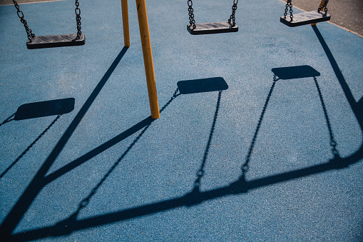 Shadows Of Swings On A Safety Playground