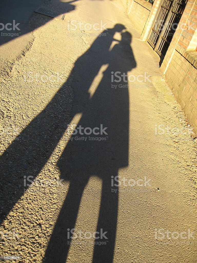 Shadows of two kids kissing in the evening royalty-free stock photo