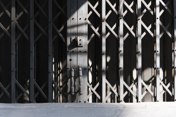 Shadows on grey security gate across shopfront stock photo