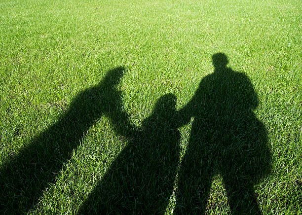 Shadows on the lawn of a family stock photo