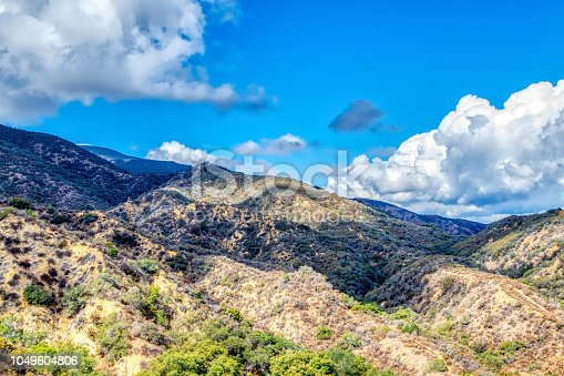 Recent rain showers leave white clouds and blue sky over Southern California mountains with hiking trails and autumn weather.