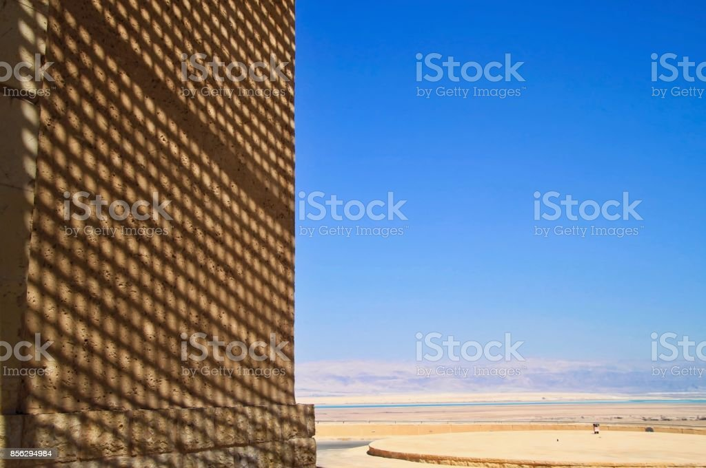 Shadows reflect on a wall at the Masada archaeological ruins, with a view of the Dead Sea and Jordanian mountains in background stock photo