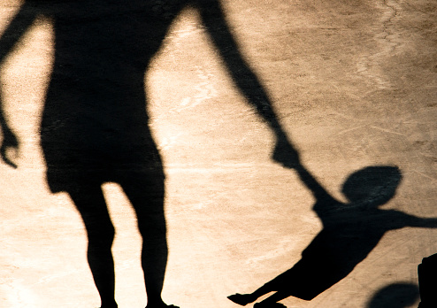 istock Shadows silhouettes of mother and child on summer promenade 1029762432