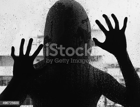 istock Shadowy figure with a knife behind glass,soft focus 496725600