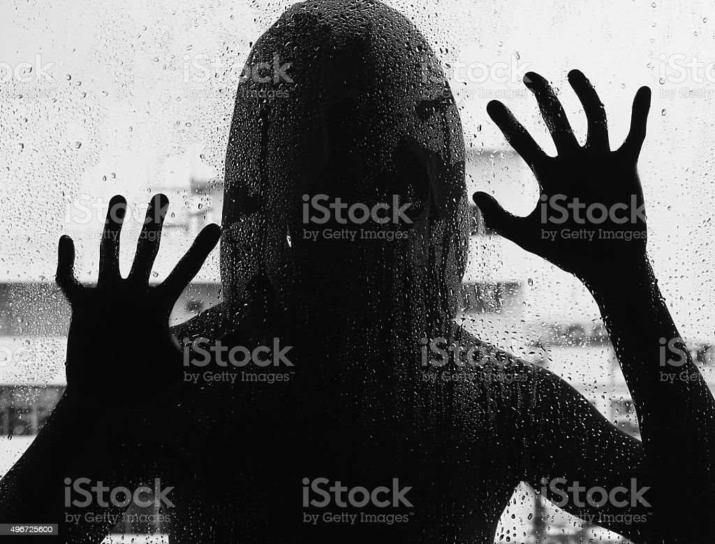 Shadowy figure with a knife behind glass,soft focus stock photo
