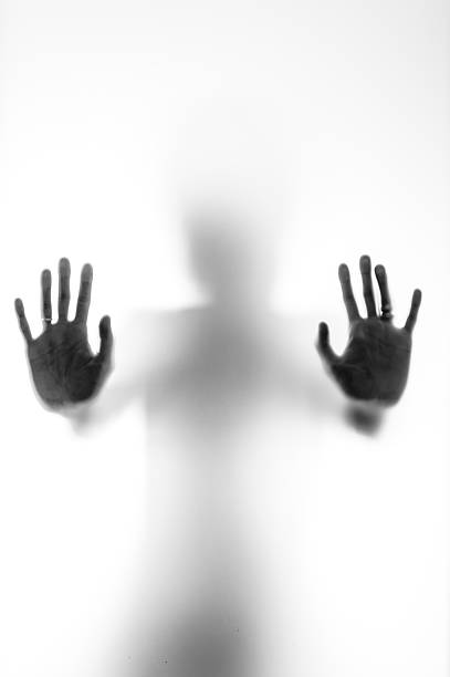 Shadowy human figure behind a frosted glass stock photo