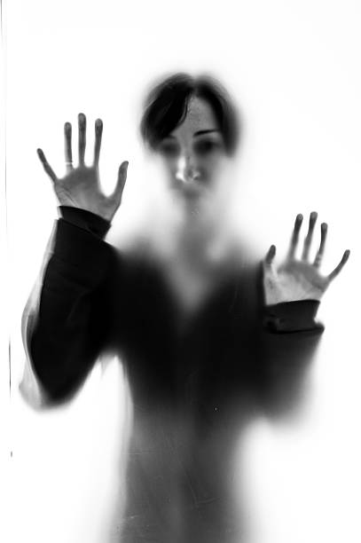 Shadowy woman figure behind a frosted glass stock photo
