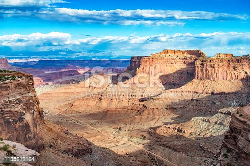 Stock photograph of Shafer Canyon in Canyonlands National Park and the La Sal Mountains in the distance, Utah, USA at sunset.