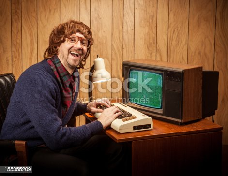 A vintage 80's looking nerd geek man at his obsolete vintage commodore vic-20 64 computer.  There is basic programming code on the screen.