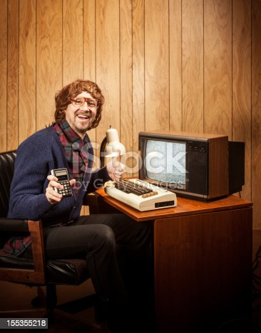 618210072 istock photo Shaggy haired Geeky Nerd Man with vintgae computer and calculator 155355218