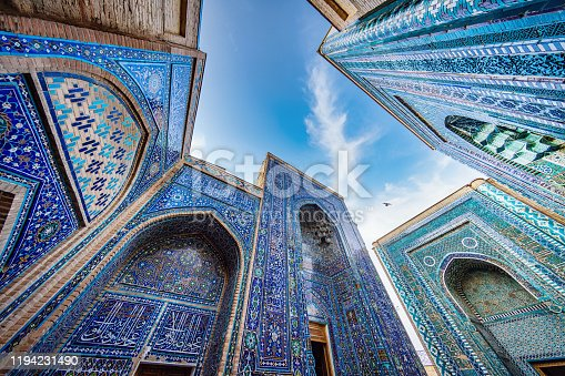 Shah-i-Zinda Mausoleum. ornamental Mosaiq Tile Ritual Building Iwans and Entrance Gates from the 9th-14th century at the famous Shahi Zinda - Shohizinda Necropolis Mausoleum from below against the sky. Ultra Wide Angle Architecture Shot. Samarkand, Silk Road, Uzbekistan, Central Asia