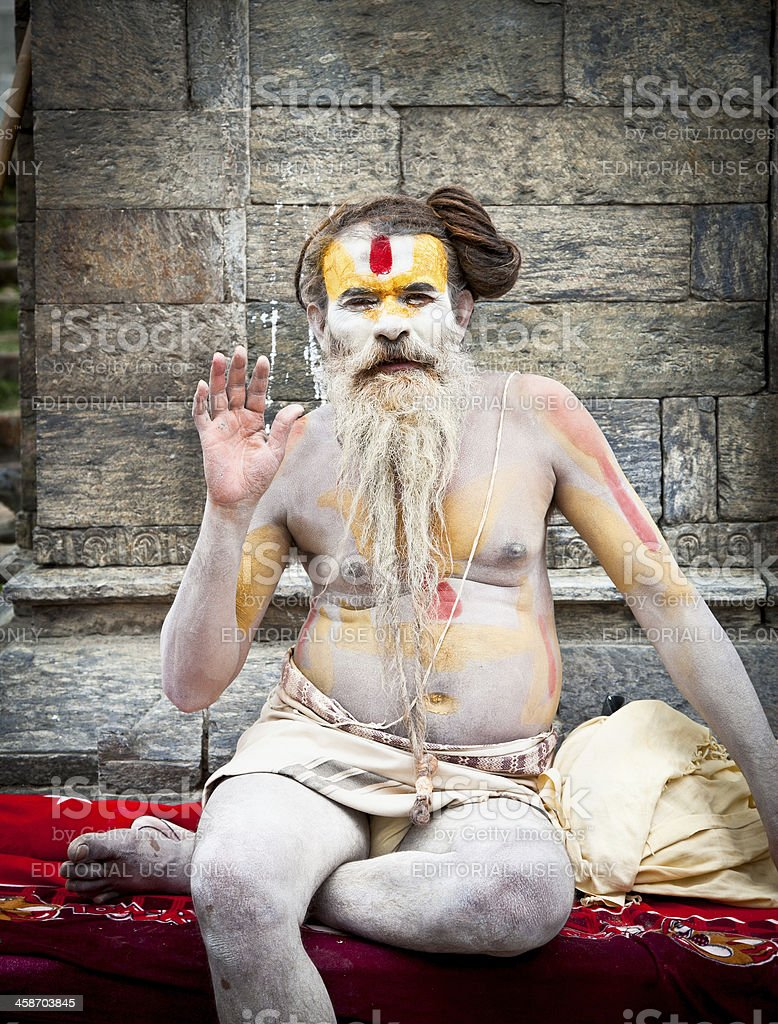 Shaiva sadhu seeks alms on the Pashupatinath Temple in Kathmandu royalty-free stock photo