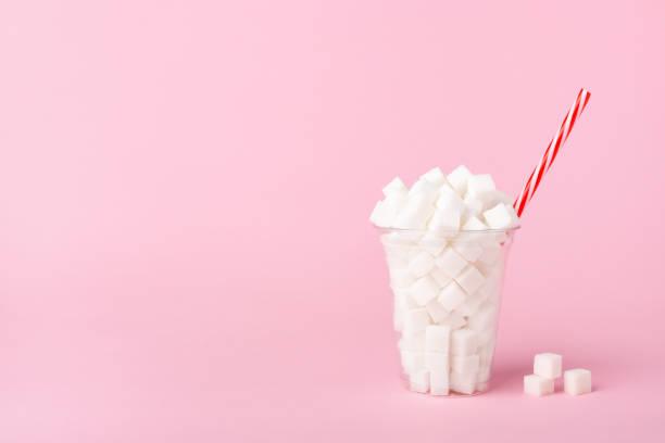 Schüttelglas voller Zuckerwürfel auf rosa Hintergrund Ungesunder Lebensmittel-Konzept – Foto