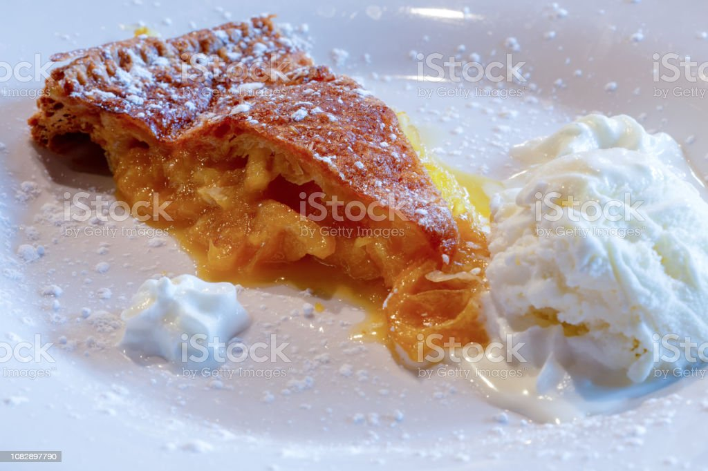 Shaker lemon pie, also known as Ohio lemon pie with vanilla ice cream, whipped cream and powdered sugar on a white plate. stock photo