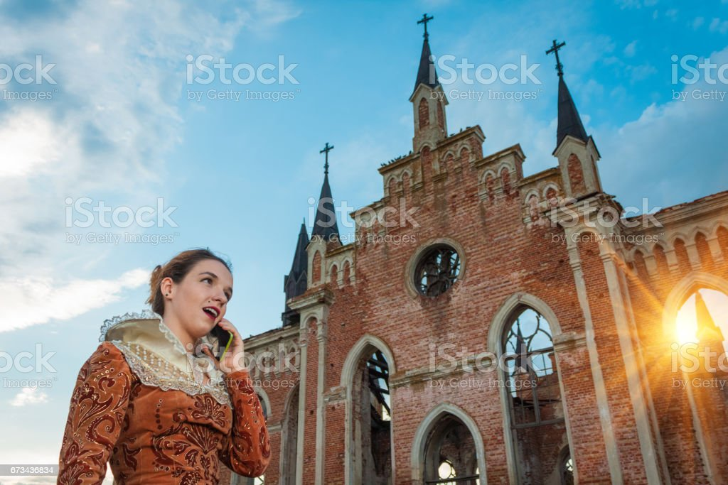 Shakespearean Woman on Smartphone Near Church stock photo
