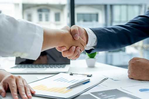 Shaking hands after businesswoman and businessmen team meeting to plan strategies to increase business income. Have a brainstorming graph analysis and discussing for the new target success.