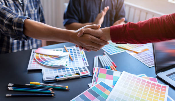 Shaking hands after meeting small group of graphic designer friendship in co-working space workplace. stock photo