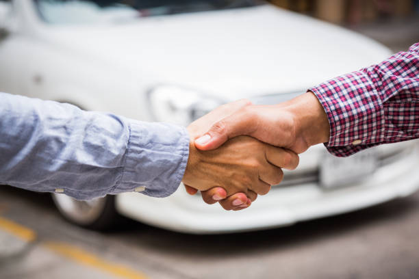 shaking hands on car background. - used car selling stock pictures, royalty-free photos & images