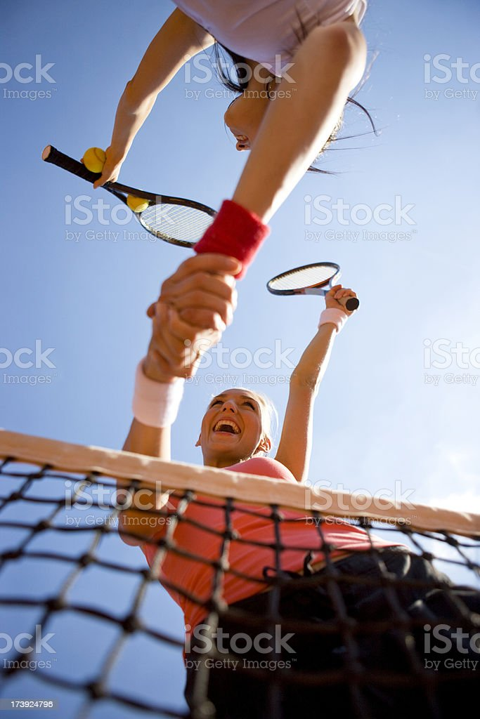 Shaking hands over tennis net stock photo