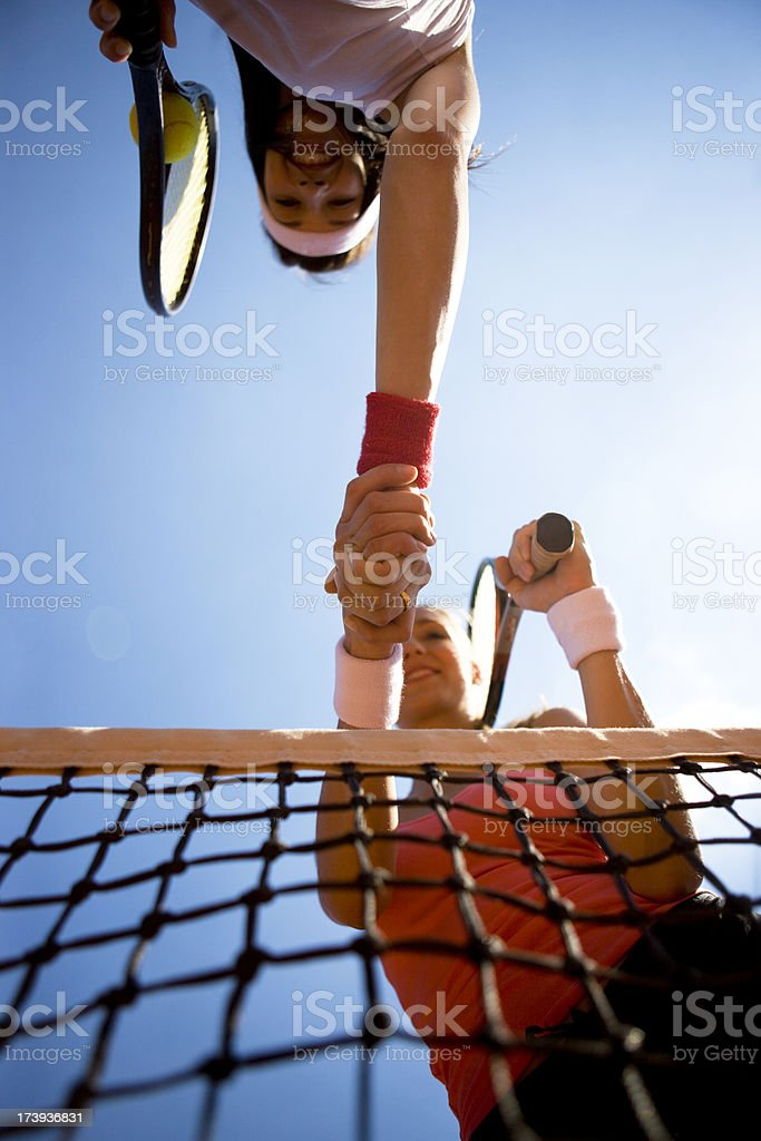 Shaking hands over tennis net royalty-free stock photo
