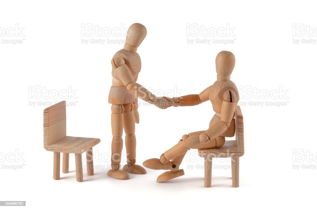 Shaking hands - wooden mannequin meeting stock photo