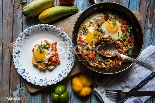 Shakshouka, a middle eastern delicacy served on a white plate from a pan