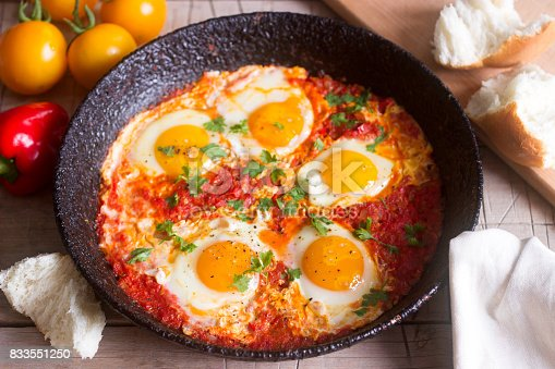istock Shakshuka with bread on a wooden table. Middle eastern traditional dish. Homemade. Selective focus. 833551250