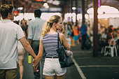 Young couple are exploring Queen Victoria Market in Australia. They are holding hands and the woman is looking out oft he frame to something she is tempted to buy.
