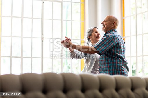 Argentinian, married, elderly couple dancing during at home