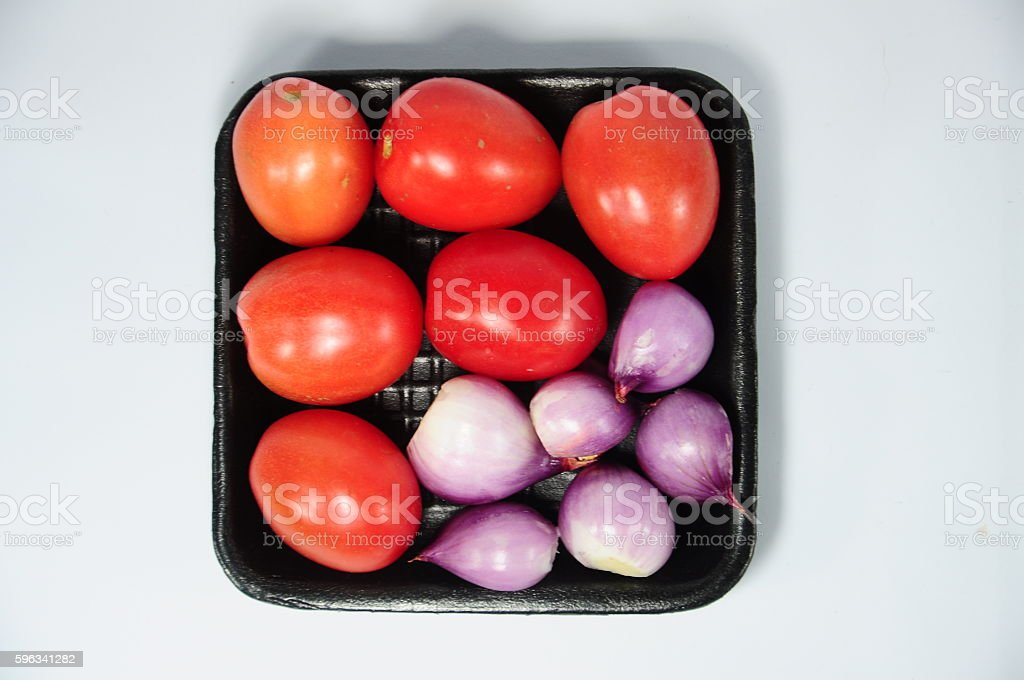 Shallots and red tomatoes on black tray royalty-free stock photo