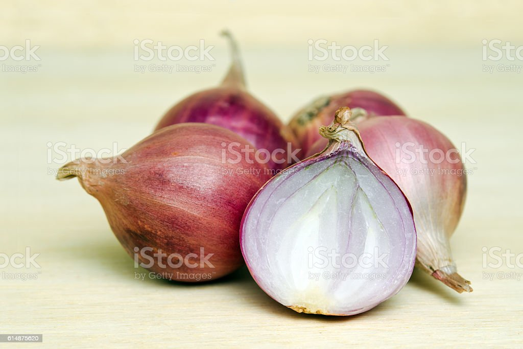 Shallots, onions, isolated on wood background stock photo