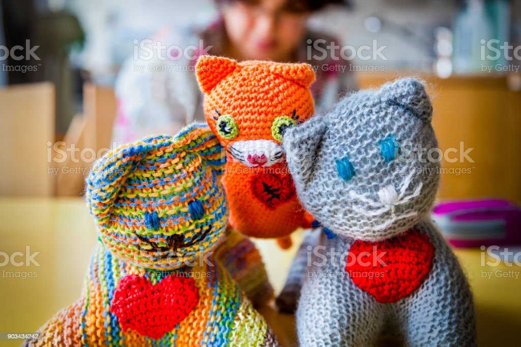 Shallow depth of field of three  knitted stuffed toy cats with red hearts. stock photo